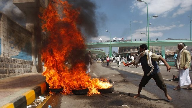 A protester sets a tire on fire during clashes with police near the U.S. Embassy in Sanaa, Yemen, Friday, Sept. 14, 2012, as part of widespread anger across the Muslim world about a film ridiculing Islam's Prophet Muhammad. (AP Photo/Hani Mohammed)