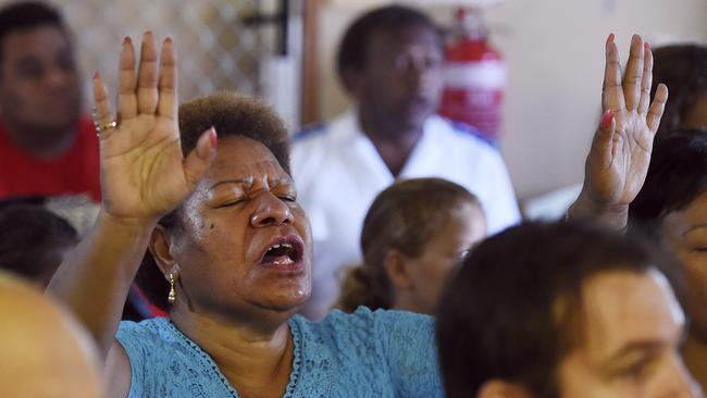 Community mourns ... a woman prays during a church service to remember the eight children. Picture: AP