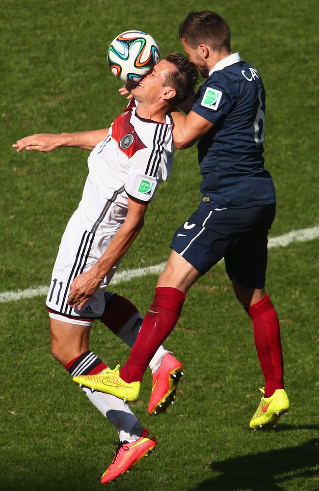 Germany's Miroslav Klose cops a ball to the face while competing with France's Yohan Cabaye.