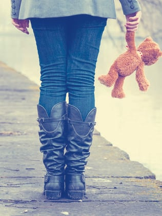 A lonely girl holding a teddy bear.