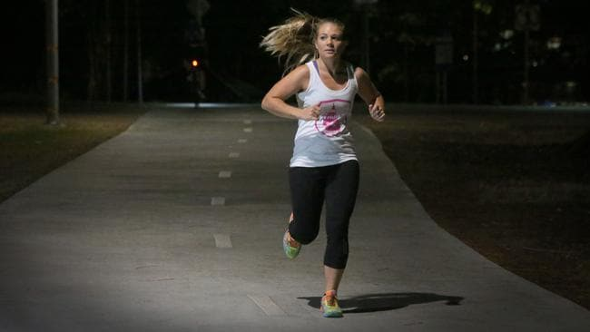 Roxy Van Tuyl runs along a lowly lit pathway along the Brisbane River. Pic: Jamie Hanson