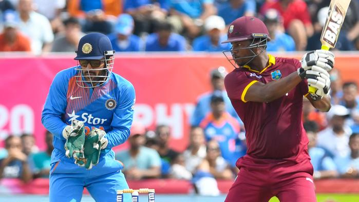 Johnson Charles (R) of West Indies hits 6 during the 1st T20i between West Indies and India at Central Broward Stadium in Fort Lauderdale, Florida, on August 27, 2016. The keeper is MS Dhoni (L) of India. / AFP PHOTO / Randy BROOKS