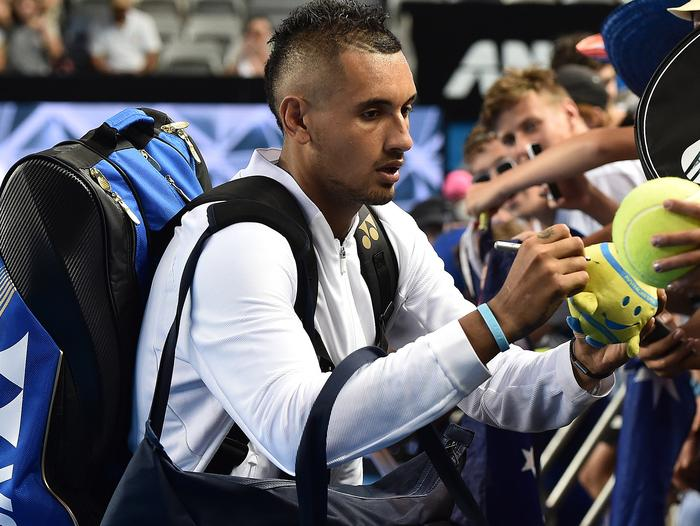 Nick Kyrgios of Australia signs autographs for fans after defeating Pablo Carreno Busta.