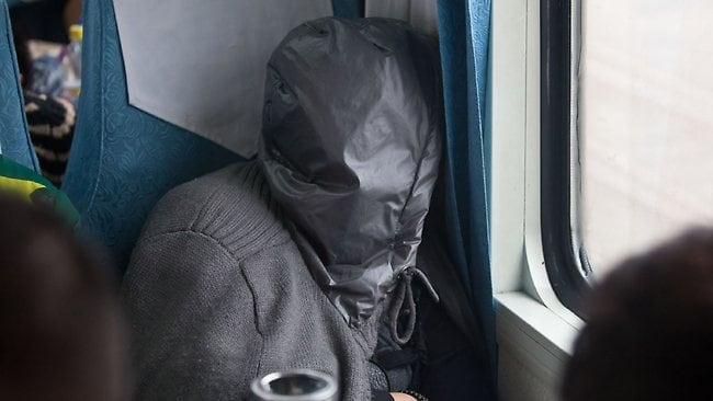 A man sleeps with his head fully-covered on the train from Guangzhou to Changchun. Picture: AFP