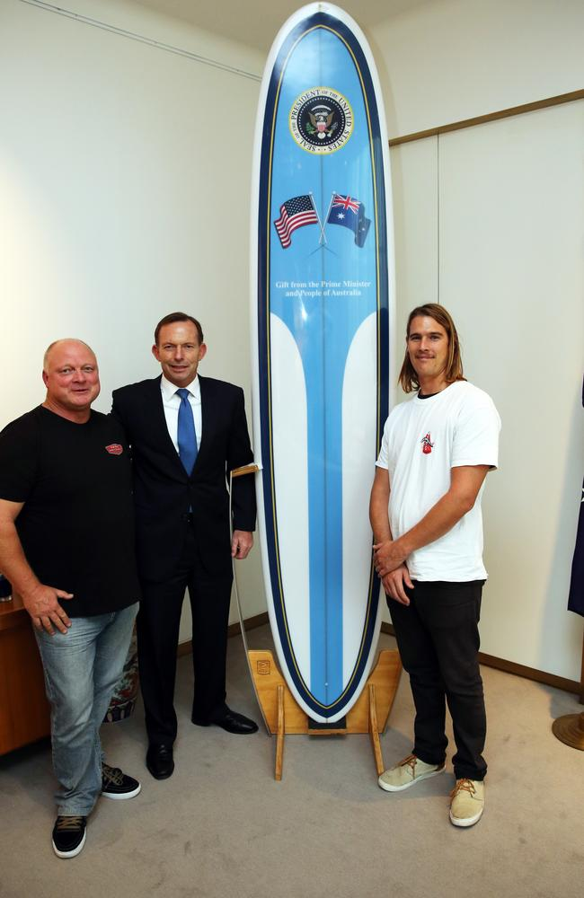 Prime Minister Tony Abbott with Greg Bennett and Tom Wentworth from Bennett Surfboards as they deliver the Long Board for US President Barack Obama.