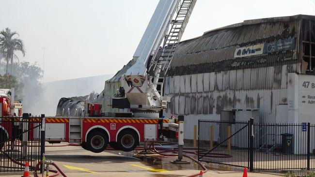 Smoke continues to billow from the gutted food supply warehouse well into the morning