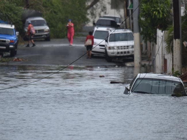 A car is viewed stuck in a flooded street in Santurce, in San Juan, Puerto Rico. Picture: AFP