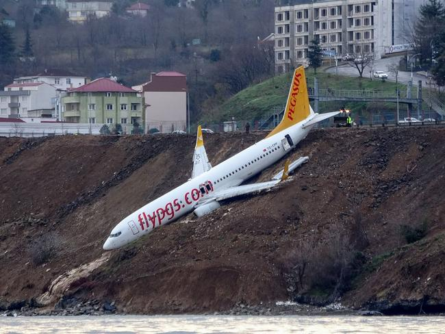 A Pegasus Airlines Boeing 737 passenger plane is seen struck in mud on an embankment, a day after skidding off the airstrip, after landing at Trabzon's airport on the Black Sea coast on January 14, 2018. Picture: DOGAN NEWS AGENCY / AFP