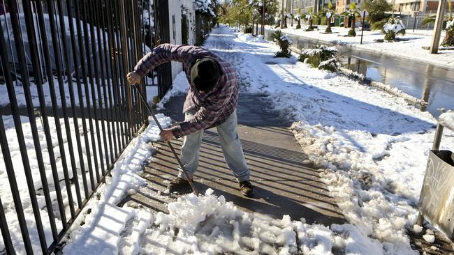 Marcelo Elias, 43, cleans snow and ice off the sidewalk in front of house in Santiago, Chile. Record cold temperatures and an unusual snowfall hit Chile's capital Saturday. Picture: AP Photo/Esteban Felix.