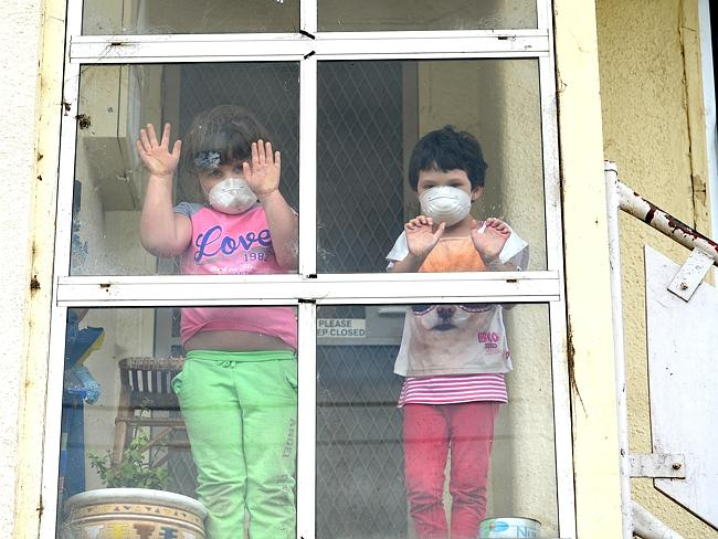 Breathing masks: Sherridan Newman, 4 and Sheniqua Gunton,5 are moving out to Inverloch with their families because of the crisis. Picture: Mike Keating