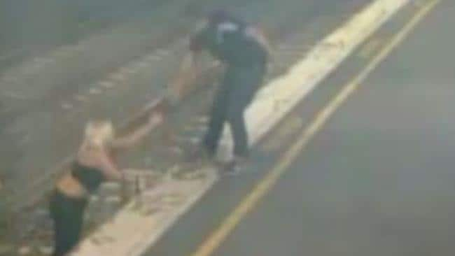 A man helps a woman up from the tracks. Picture: Victoria Police