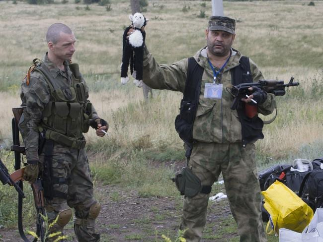 A pro-Russian fighter holds up a toy found among the debris at the crash site of MH17. (AP Photo/Dmitry Lovetsky)