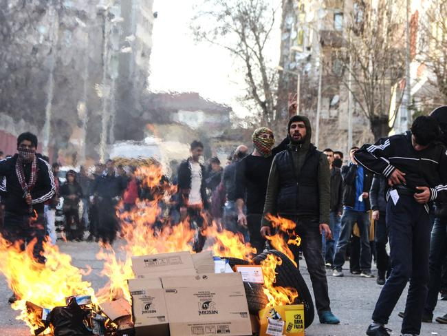 Protesters stand next to a fire during clashes between Turkish forces and Kurdish people in the centre of Diyarbakir, as they protest against the curfew earlier this month.