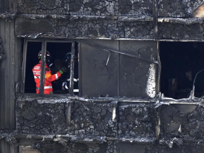 Emergency workers and police inspect inside the remains of Grenfell Tower. Picture: AFP