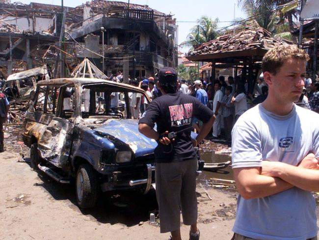 Targeted attacks ... Foreign tourists stand at the scene of the car bomb blast in Kuta in 2002. Picture: AP