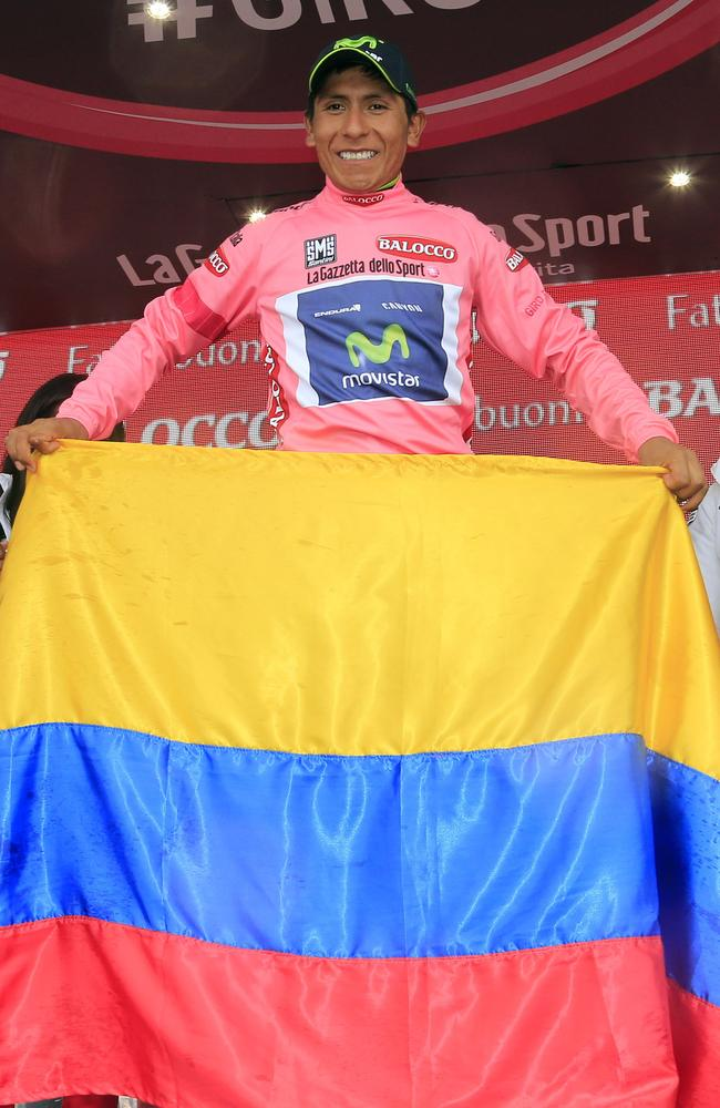 Colombian cyclist Nairo Quintana celebrates with the pink jersey and his nation's flag.