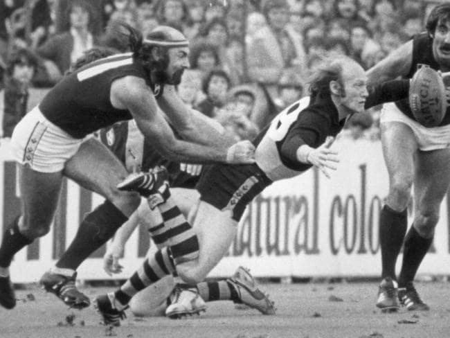 Kevin Bartlett drops the ball as Bruce Doull tackles and Val Perovic looks on.