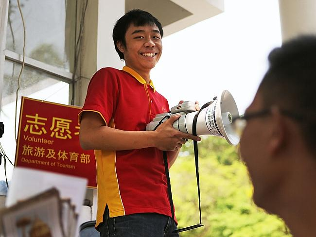 Mandarin speaking volunteers use bullhorns to get the attention of Chinese tourists at Chiang Mai University.