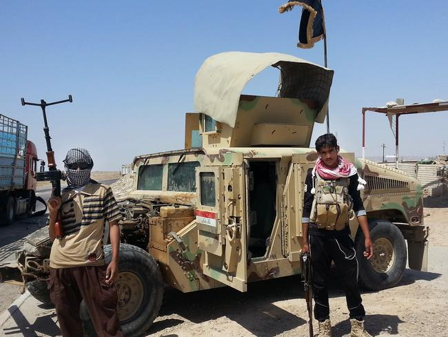 Militants stand with a captured Iraqi Army Humvee at a checkpoint some 250 kilometres north of Baghdad, Iraq.
