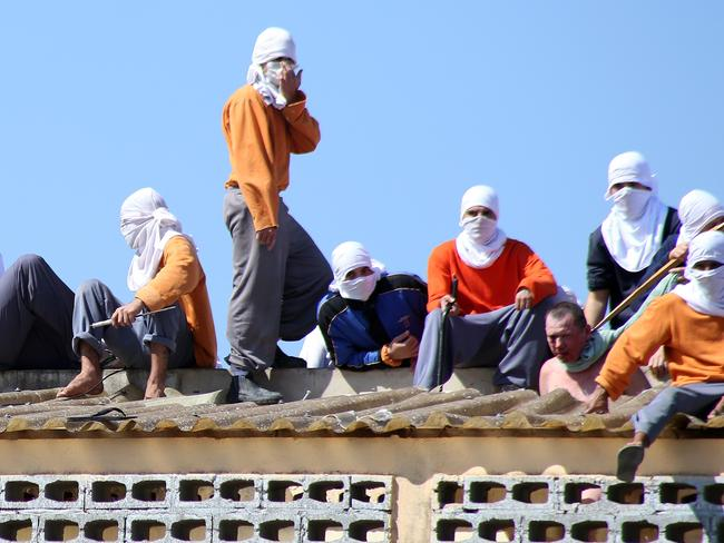 Inmates on the roof of the penitentiary hold a hostage (2nd left) in Cascavel, Brazil. Picture: Marcelino Duarte