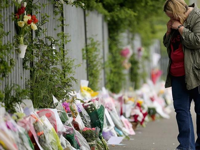 Grieving ... flowers and letters have been left outside Corpus Christi Catholic College a