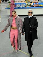 PARIS FASHION WEEK 2014: Fashion Designer Karl Lagerfeld and model Cara Delevingne appear at the end of the runway during the Chanel show. Picture: Getty