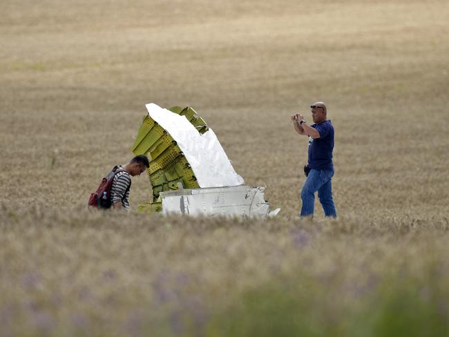 Parts missing .... Malaysian air crash investigators take pictures of wreckage at the crash site. Picture: Vadim Ghirda