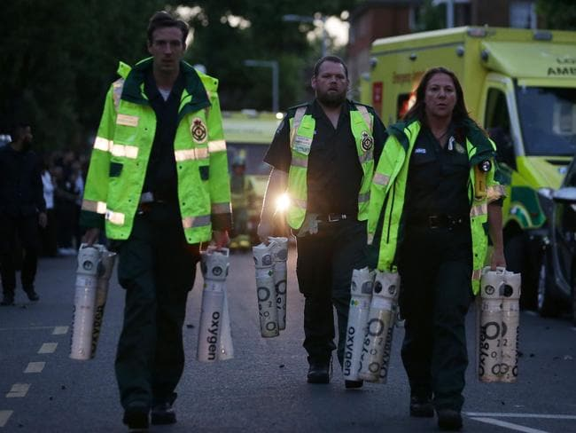 Members of the emergency services carrying oxygen tanks. Picture: AFP PHOTO
