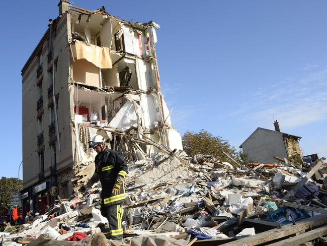 A firefighter searches through the rubble of a four-storey residential building that collapsed following a blast in Paris. AFP PHOTO / BERTRAND GUAY