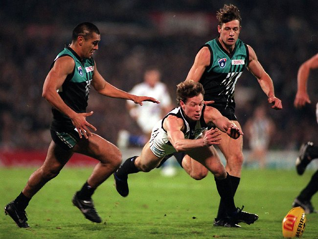 Collingwood stalwart Gavin Brown dives for the ball under pressure from Port Adelaide's Donald Dickie and Matthew Primus. Picture: Ray Titus