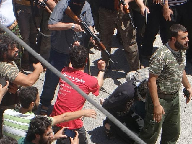 Crowd looks on ... one even has a phone out to capture the execution by rebel fighters. Picture: AMR RADWAN AL-HOMSI