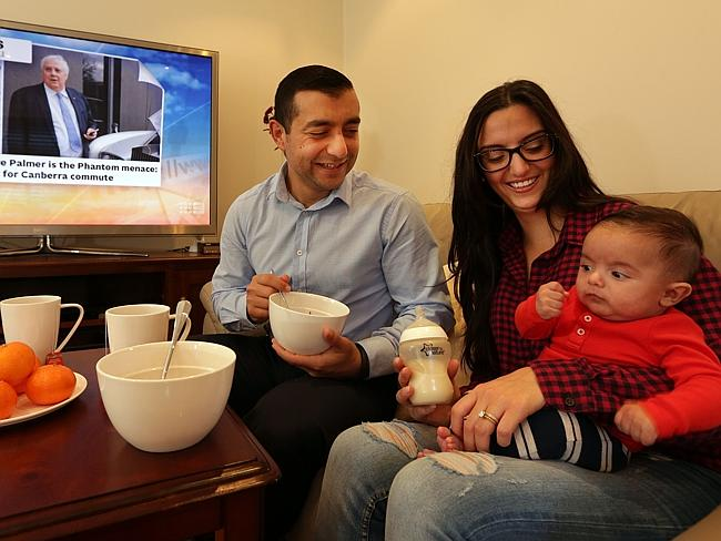 Little time ... Sylvia Baraya and Anthony Baraya with their son Victor (3 months) having their breakfast in front of the TV at their home in Guildford.