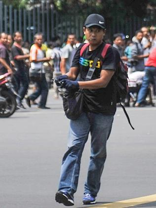 One of the attackers ... with a gun walks in the street as people run near Sarinah shopping mall. Picture: AP