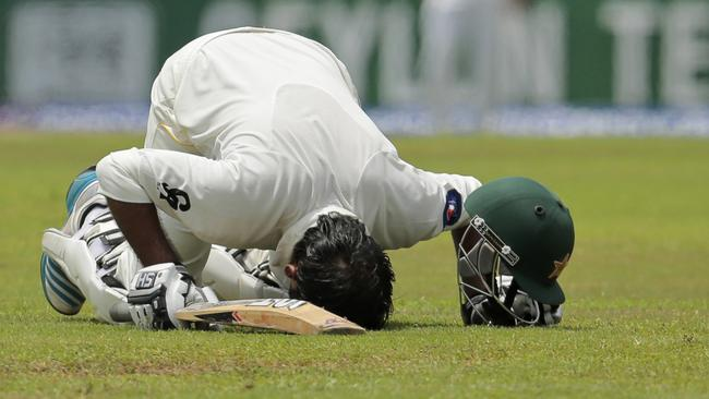 Pakistani batsman Sarfraz Ahmed kisses the ground as he celebrates his century.