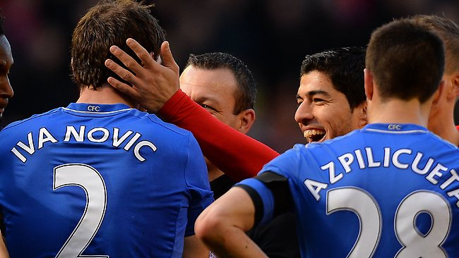 Liverpool's Luis Suarez pats Chelsea's Branislav Ivanovic on the head after the Chelsea player complained to referee Kevin Friend about being bitten during the English Premier League 2-2 draw at Anfield. Picture: Andrew Yates