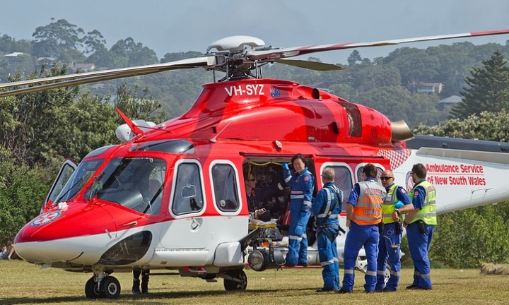 Palm Beach,Australia - January 1,2015: An air ambulance prepares to take a young man to hospital. The man had to be resuscitated after jumping off a rock into the ocean.