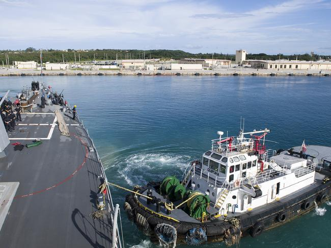 A harbour tug boat assists the Arleigh Burke-class guided-missile destroyer USS Sterett (DDG 104) as the ship departs Naval Base Guam on August 9. Picture: AFP/US NAVY/Byron C Linder