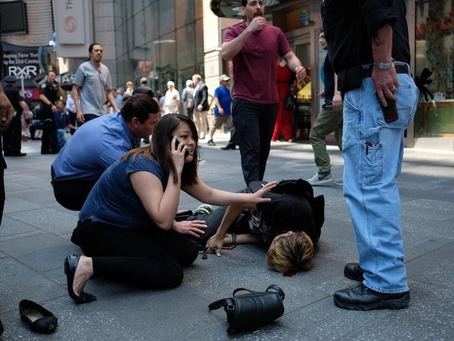 People attend to an injured man after a car plunged into him in Times Square in New York. Picture: AFP.
