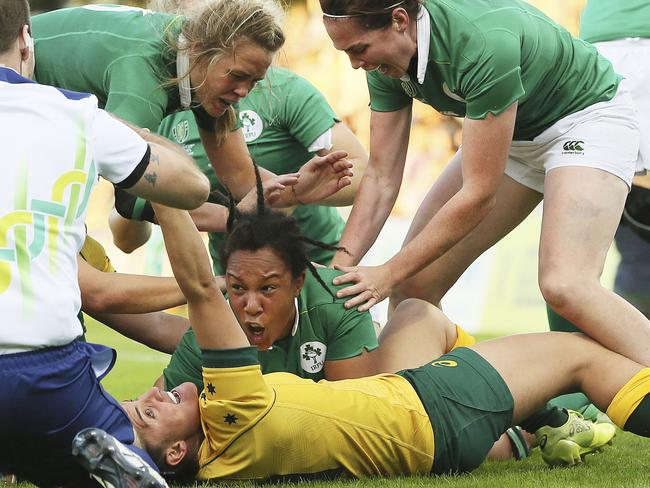 Ireland's Sophie Spence, centre, celebrates as she scores her side's third try in the opening match of the World Cup against Australia.