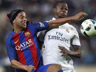 Former FC Barcelona player Ronaldinho, left, fights for the ball with former Real Madrid player Cesar Correa, right, during a friendly soccer match between FC Barcelona and Real Madrid legends, at the Camille Chamoun Sports City in Beirut, Lebanon, Friday, April, 28, 2017. (AP Photo/Hussein Malla)