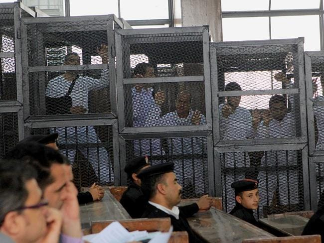 On trial ... Jazeera English bureau chief Mohamed Fahmy, left, producer Baher Mohamed, second left, and correspondent Peter Greste, centre, stand inside the defendants' cage in court. Picture: AFP