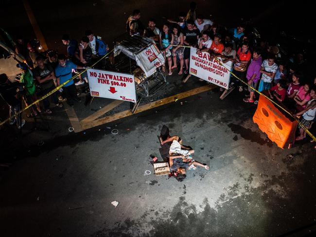 An alleged drug dealer lies dead in a Manila street next to a cardboard sign carrying his 'confession'. Picture: Getty Images