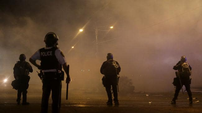 A law enforcement officer watches as tear gas is fired to disperse a crowd defying the Ferguson curfew. Picture: AP Photo/Charlie Riedel
