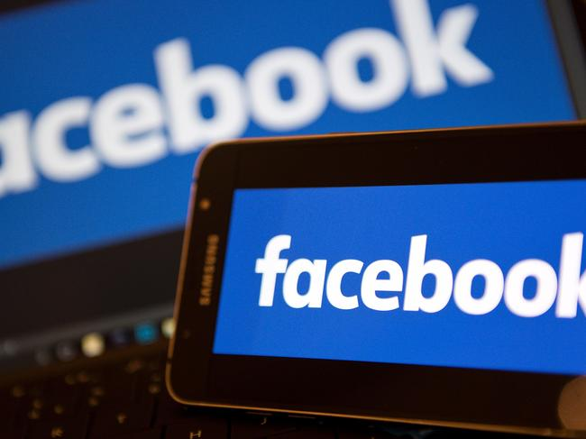 """(FILES) This file photo taken on November 21, 2016 shows  Facebook logos pictured on the screens of a smartphone (R), and a laptop computer, in central London. Facing mounting pressure to use their technological clout to curb the spread of jihadist propaganda, major US social networks have finally joined forces in an effort to curb """"terrorist content."""" Facebook, Twitter, Microsoft and Google-owned YouTube announced December 6, 2016 a drive to stop the proliferation of videos and messages showing beheadings, executions and other gruesome content, posted by the likes of the Islamic State group or Al-Qaeda. The move comes as social media giants face increasing scrutiny over their role in the explosion of so-called """"fake news"""" -- which is believed to have influenced the US election -- as well as online bullying and hate speech.  / AFP PHOTO / Justin TALLIS"""