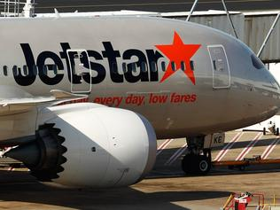 "An aircraft of Jetstar Airways, the budget arm of Qantas Airways Ltd., stands at Sydney Airport in Sydney, Australia, on Monday, June 22, 2015. Australia's central bank reiterated the need for deeper currency declines to balance economic growth that's predicted to remain below average until the latter part of 2016. ""A lower exchange rate would have an immediate beneficial effect on some sectors such as tourism,"" the Reserve Bank said in minutes of its June policy meeting. Photographer: Brendon Thorne/Bloomberg"