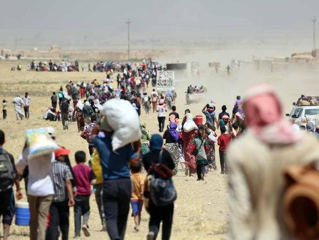 Refugees ... thousands of Yezidis trapped in the Sinjar mountains are rescued by Kurdish Peshmerga forces and Peoples Protection Unit (YPG) in Mosul. Picture: Getty