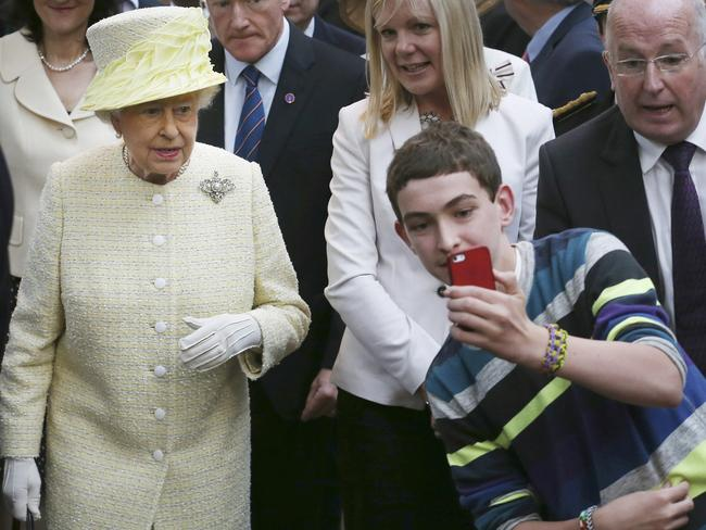 A youth blags a selfie with The Queen in Belfast. Picture: AP Photo/Peter Macdiarmid