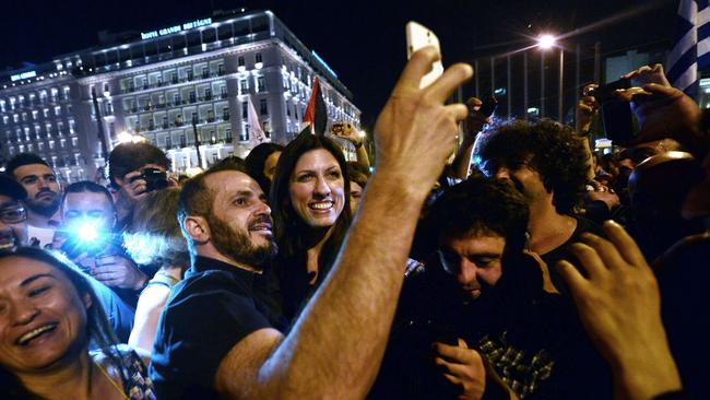 Greek parliament's president and Syriza party member Zoe Kostantopoulou, centre, takes a selfie with a 'No' supporter as she joins the celebrations in front of the parliament.