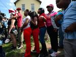 Cleveland's House of Horrors: onlookers gather to watch FBI forensic personels removing evidence from the house where three women were held captive for a decade. Photo: AFP