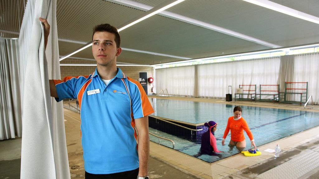 Auburn pool coordinator Jonathan Jamsek with the curtain, which gives women and children privacy while they swim. (Pic: News Corp)